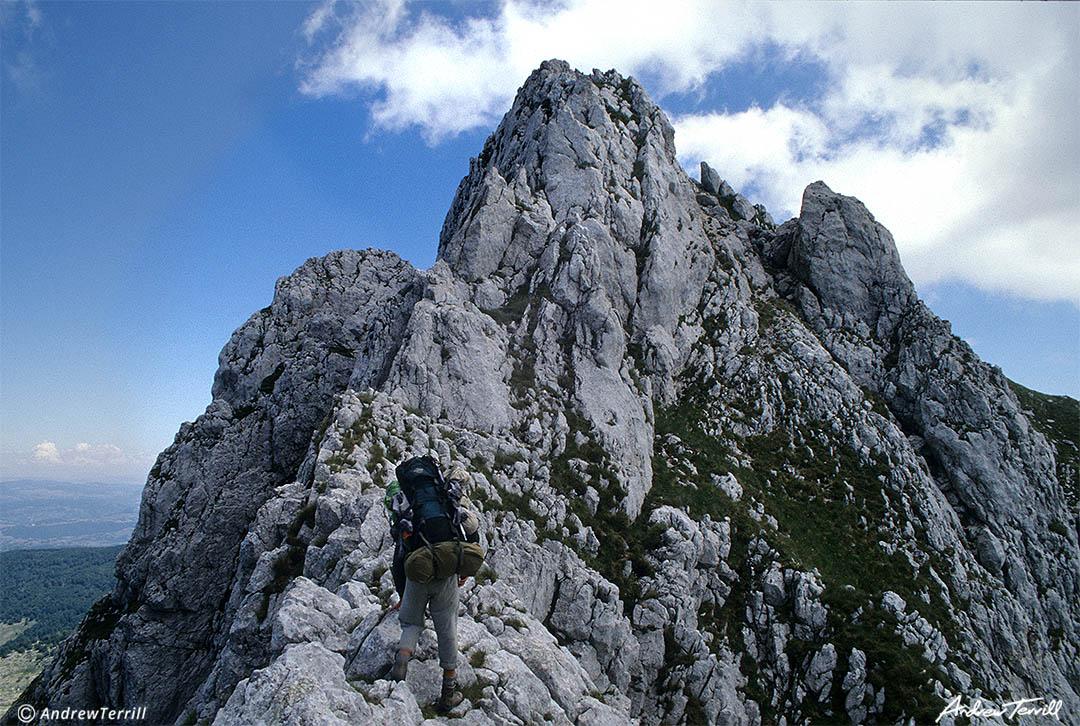 andrew terrill hiker backpacker on narrow knife edge ridge in abruzzo apennines italy