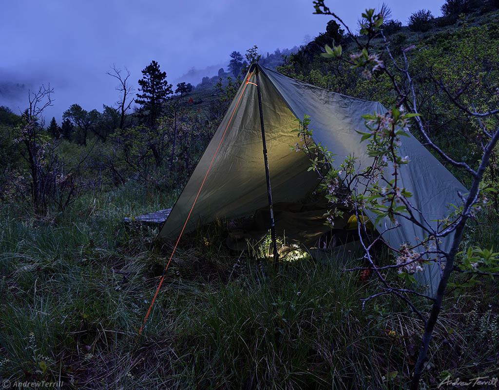 tarp wild camping in gloomy wet evening rocky mountains