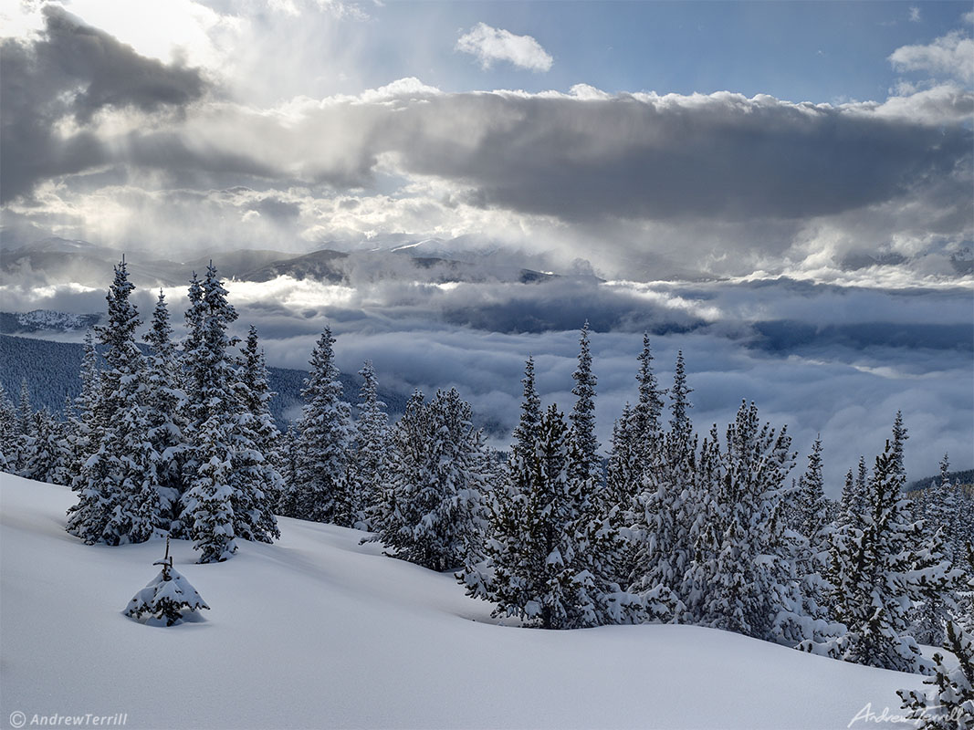 winter snow on mountains and forests in colorado above clearing storm clouds