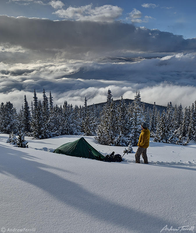 winter wild camping with tent and figure looking at view in snow with clearing storm clouds over rocky mountains in colorado