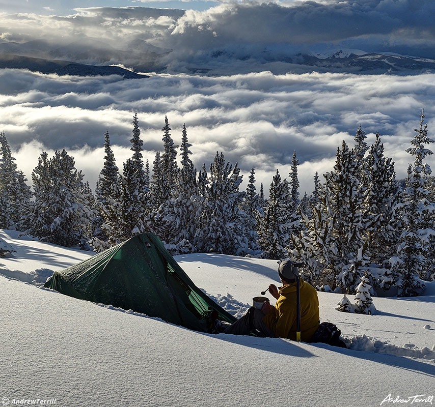 winter wild camping with tent and figure eating dinner looking at view in snow with clearing storm clouds over rocky mountains in colorado
