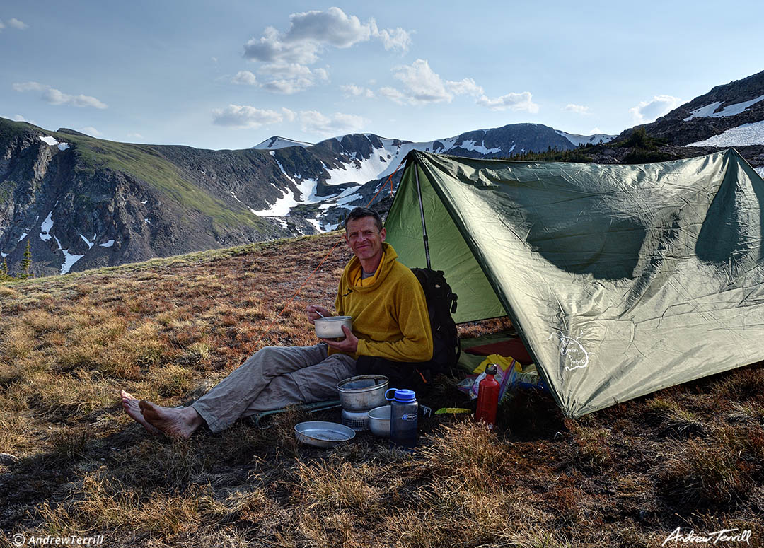 andrew terrill eating dinner in wilderness camp with tarp tent