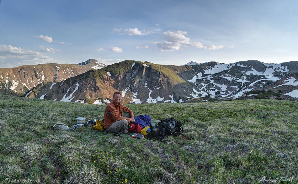 andrew terrill sitting on hillside in rocky mountains