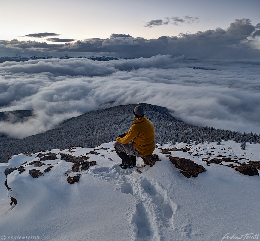 hiker sitting on mountain summit in winter in snow above the clouds