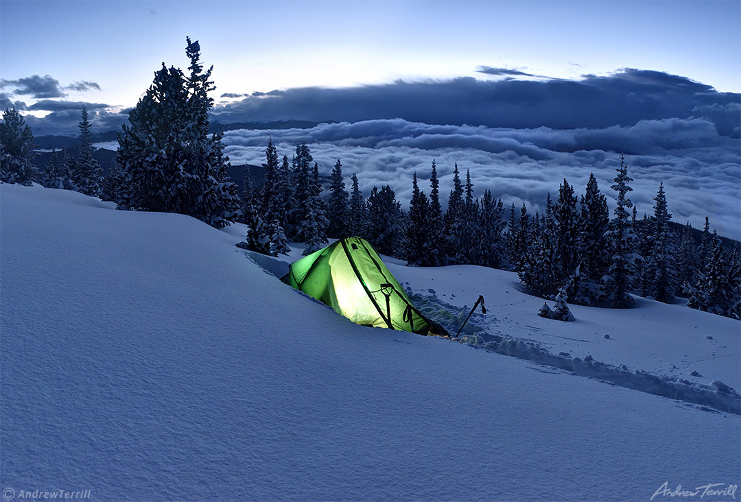 winter wild camping with glowing tent in snow with clearing storm clouds over rocky mountains in colorado