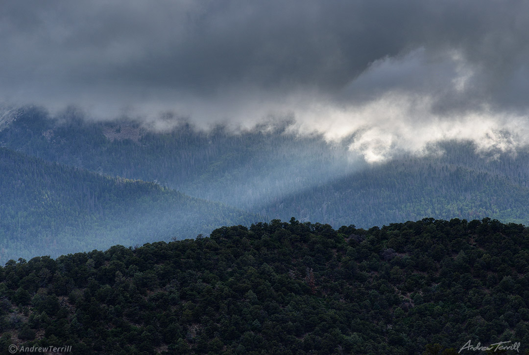 sunbeam shining over forest and mountains under storm cloud colorado
