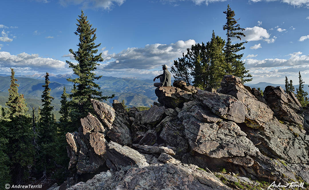 hiker sitting on rock looking at view colorado front range