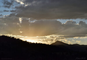 sunlight bursting over forest and mountain ridge