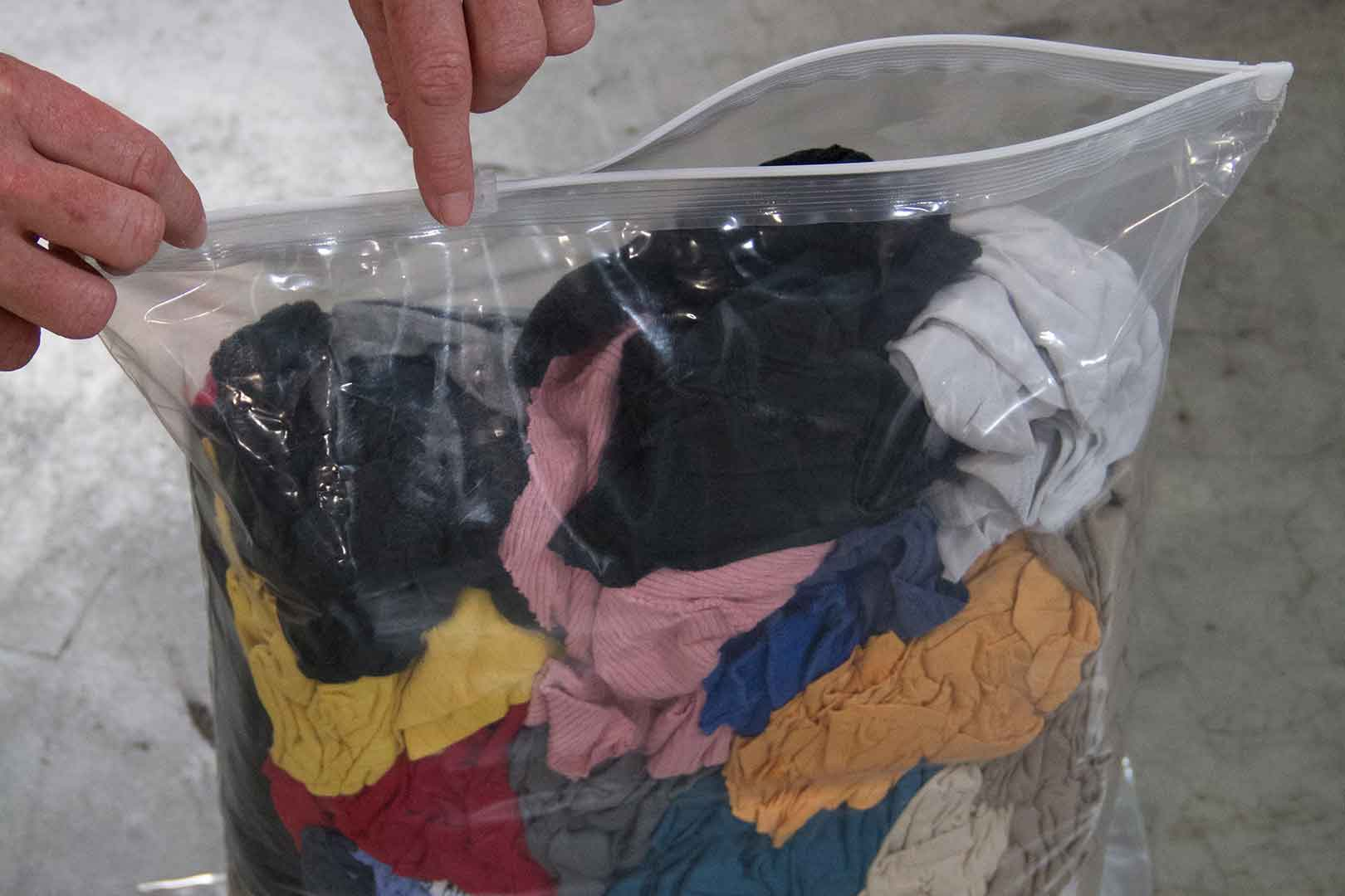 person closing bag of rags