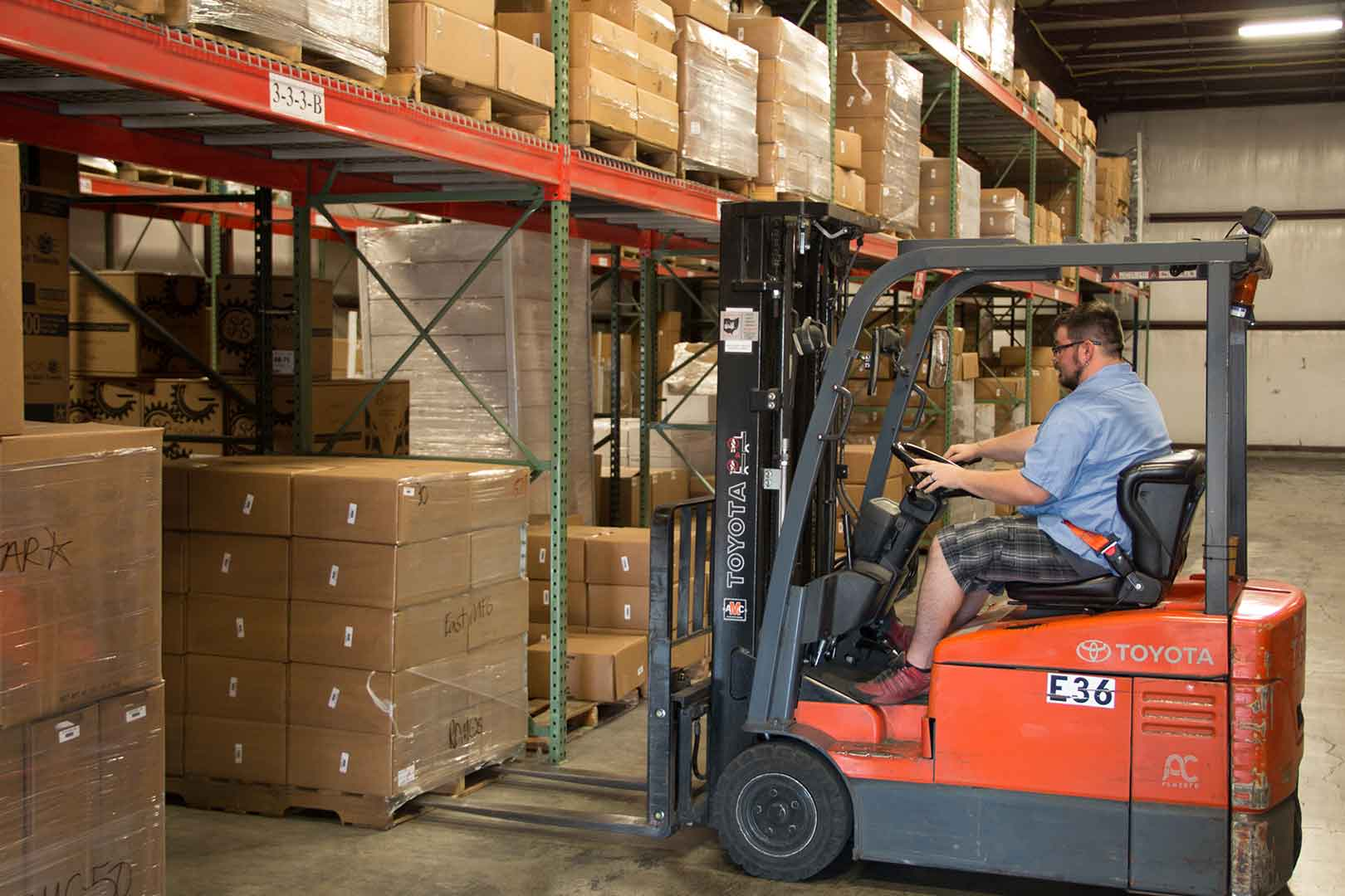 man uses forklift to move boxes in warehouse