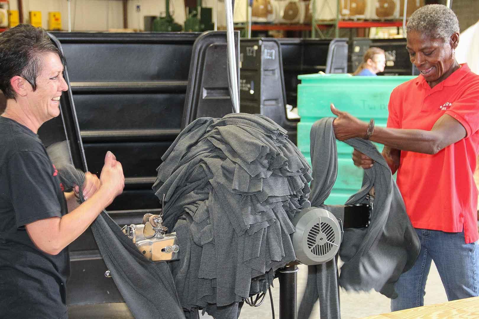 women using cutting machine to cut grey rags