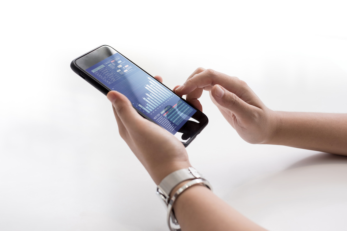 Close up female hand holding smartphone with business chart on screen
