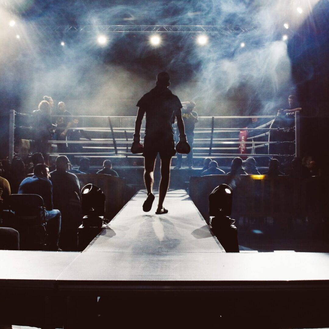 This is a picture of a boxer with gloves on walking down to the boxing ring