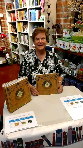female author sitting at book signing table, books in the background