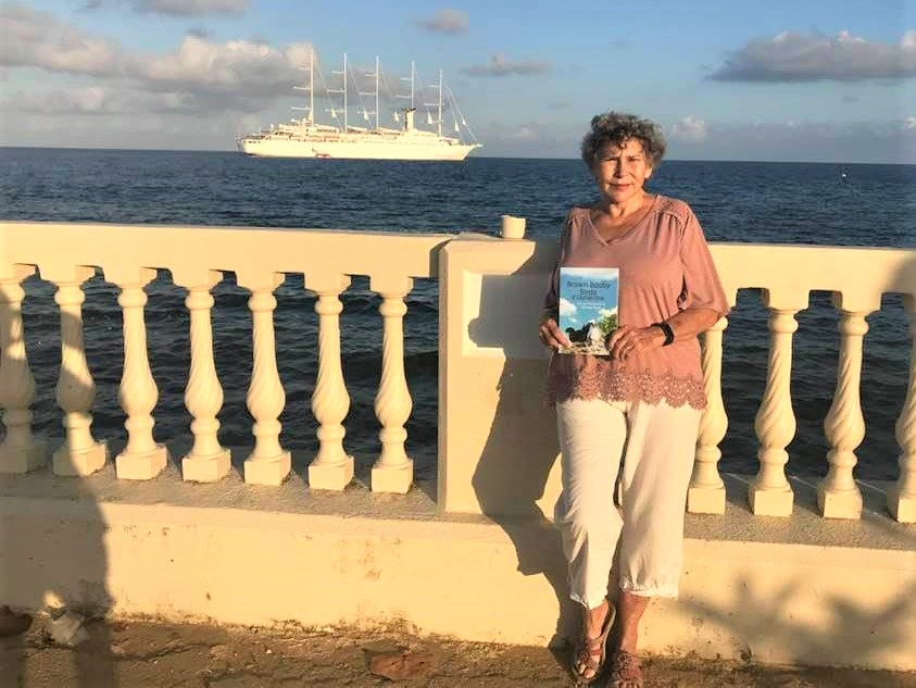 Author Bonnie Scott holding a copy of her important new book, Brown Booby Birds of Cayman Brac.