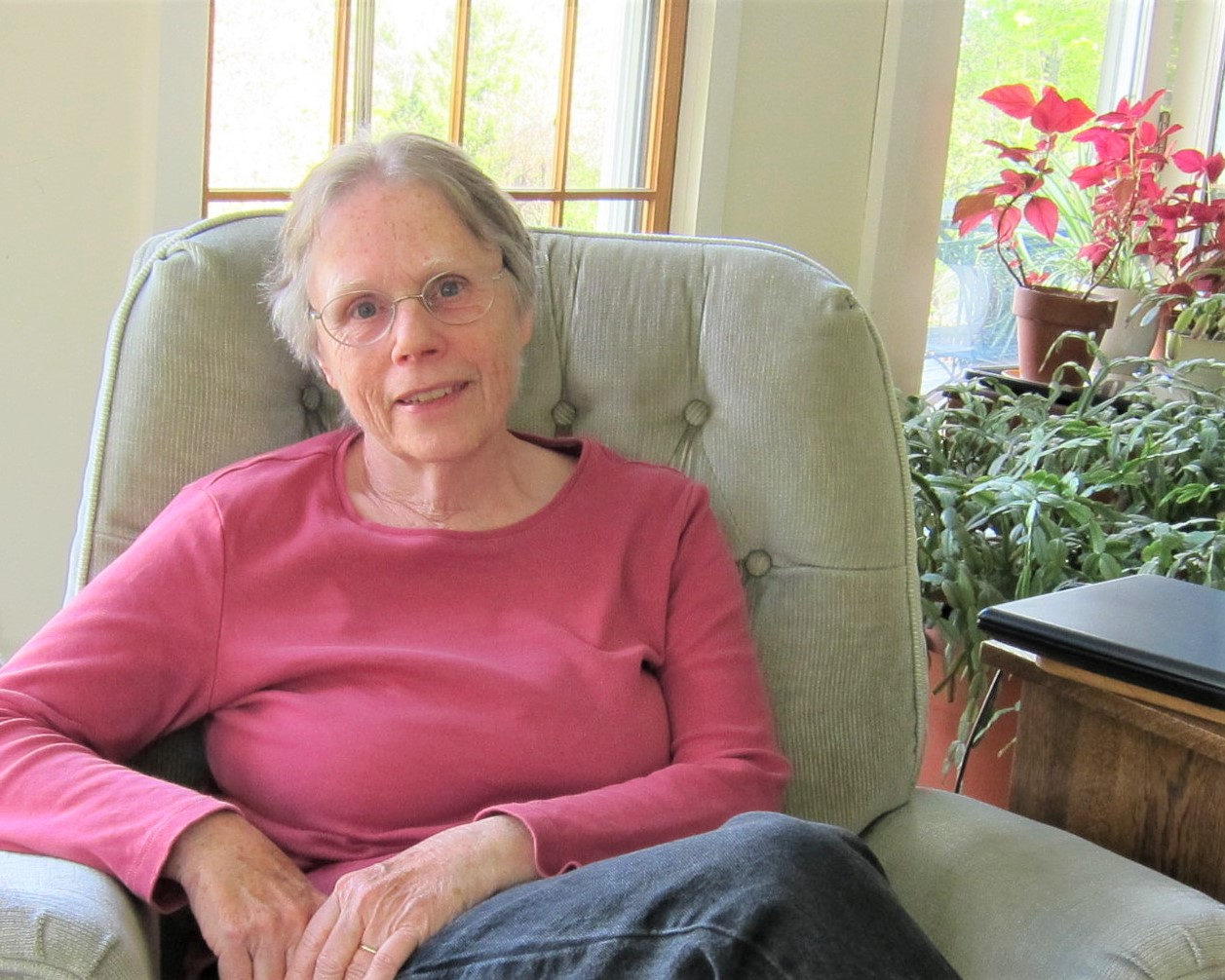 photo of author Jo Busha in a chair in front of a window