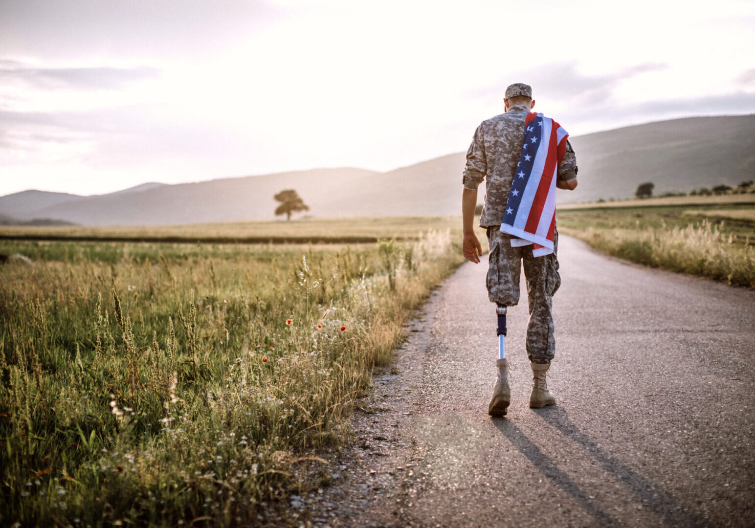 Rear View Of Young Amputee Soldier Walking Road Wearing American Flag, unrecognizable person