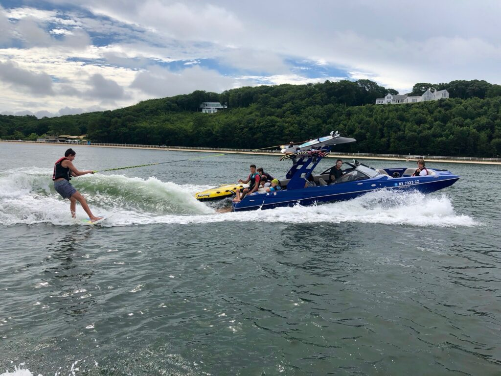 wake surfing with peconic water sports in front of sunset beach hotel during summer
