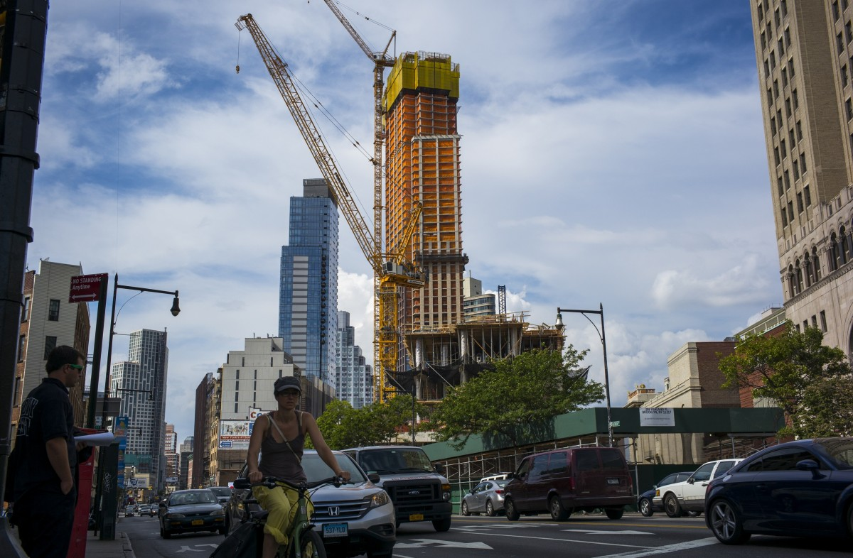 A woman bicycles past a 52-story apartment building under construction in downtown Brooklyn on Aug. 23. New York City is failing to increase its housing supply enough to meet demand. (Photo by Robert Nickelsberg/Getty Images)