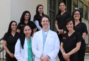 Orange, CT dental office team photo showing dentists Drs. Nick and Carla Calcaterra