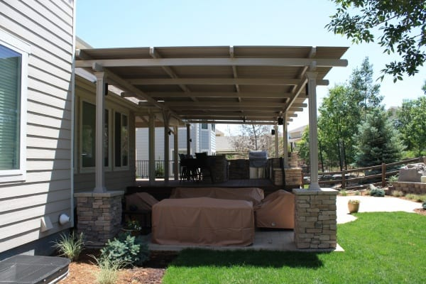 A patio with stone pillars and a cover