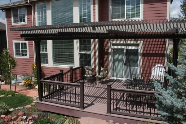 A covered wooden deck in front of a dark red house
