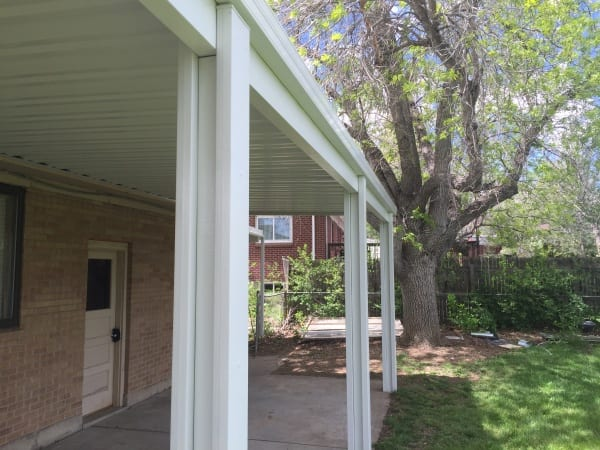 Covered patio on a yard with a tree