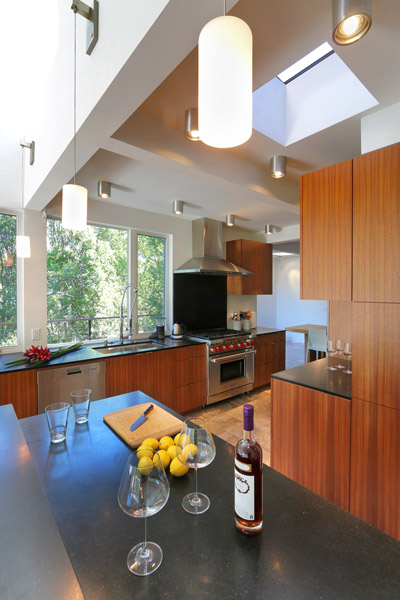 modern kitchen with pendant and canned ceiling lights, wood cabinets, black composite countertops and skylight