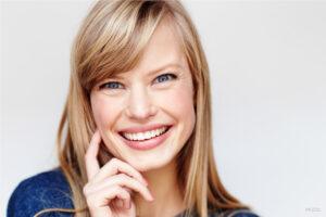 Smiling Blond Female Touching Cheek