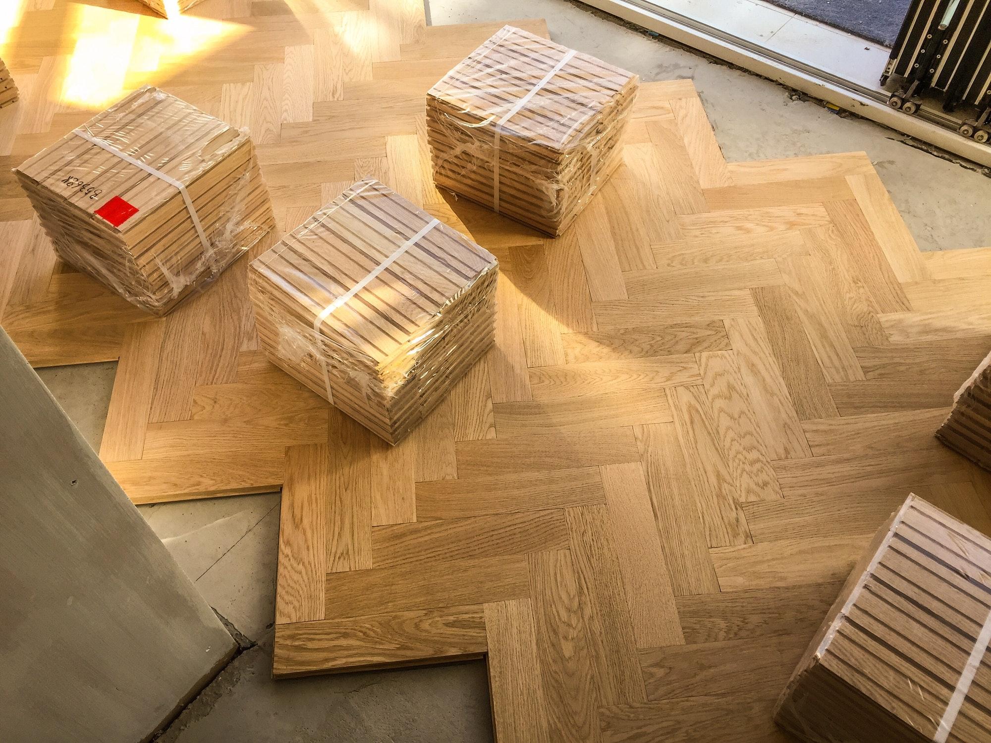 Packs of wooden parquet flooring are seen during installation of wood herringbone kitchen floor