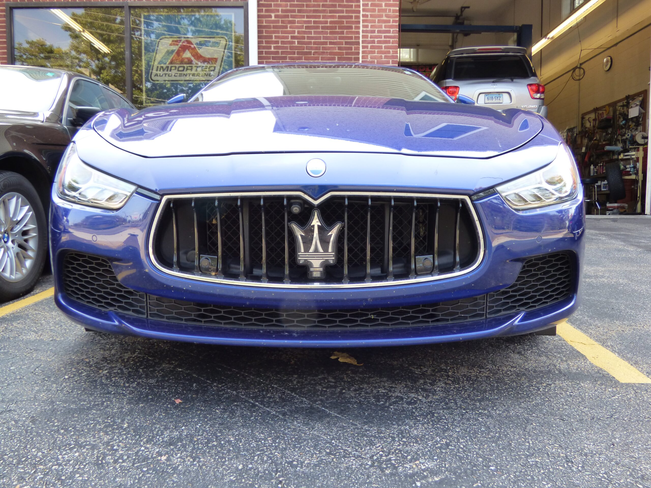 Blue Maserati parked in front of imported auto center