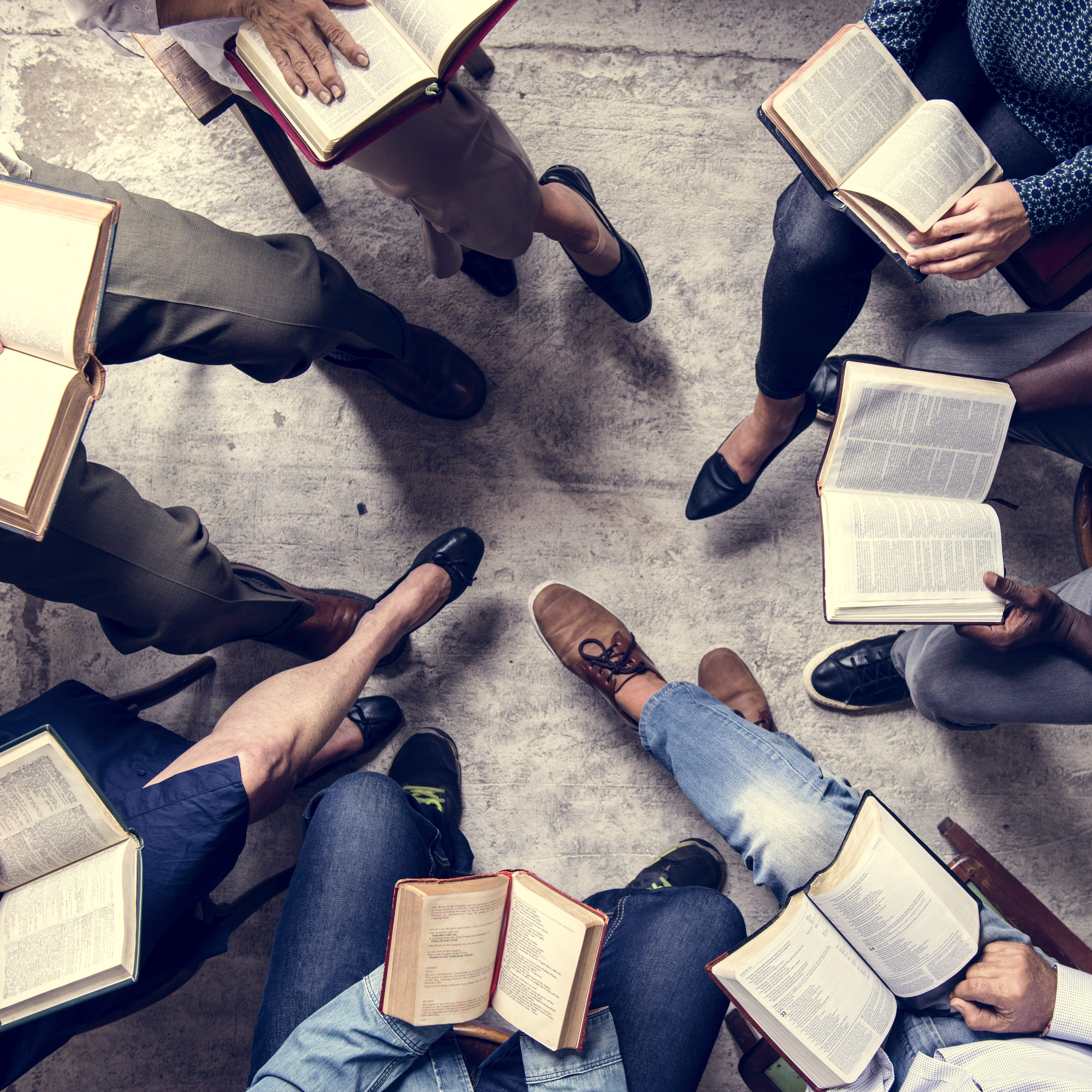 View from overhead of a book group sitting in a circle reading.