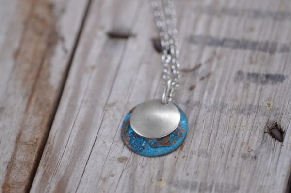 blue patina dome necklace with brushed nickel overlay necklace horizontal image on wood
