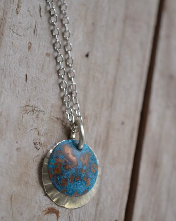 blue patina overlay on textured brushed nickel dome necklace close up vertical