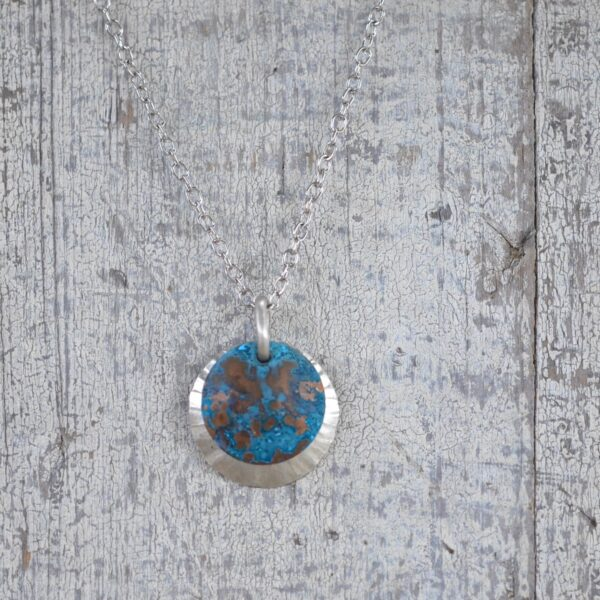 blue patina overlay on textured brushed nickel dome necklace square on white
