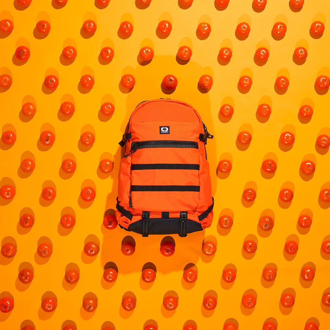 OGIO Glow Orange Color Introduction social photo. Orange Backpack with oranges all around it.
