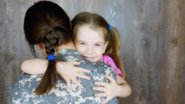 Smiling toddler hugging a woman