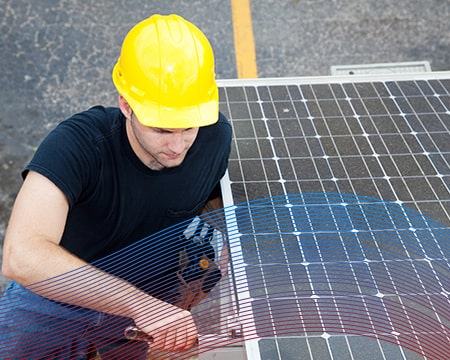 Technician with Yellow Hard Hat Fixing Solar Pannel