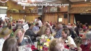 charity auction bidder raising bid paddle