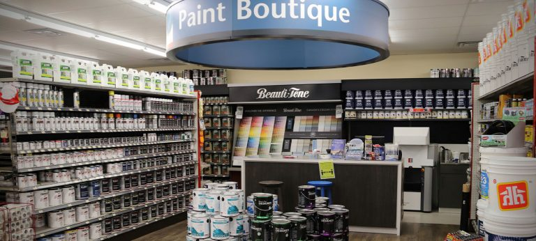 Photo of the paint center with stacks of paint cans, a wall of colourful paint chips, and a shelf of painting products