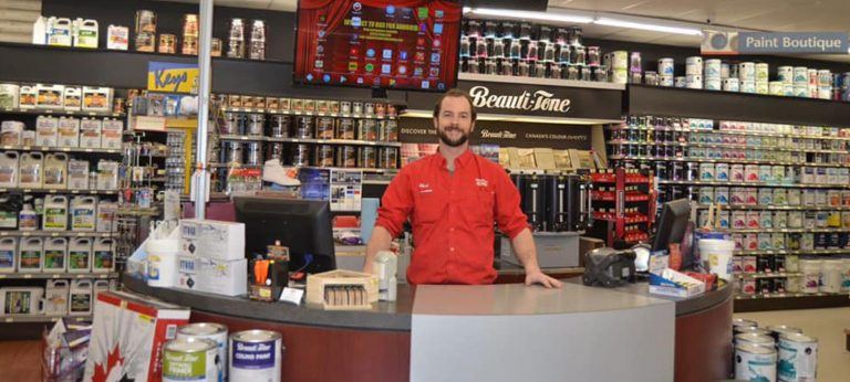 Photo of a smiling employee in a red shirt standing behind a customer service desk
