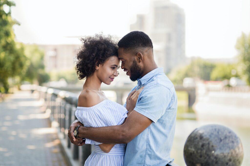 Loving african-american couple hugging on the bridge