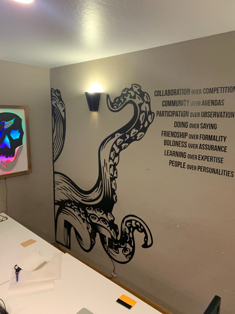 a large vinyl krakken design on the main space wall pointing to our gangplank manifesto