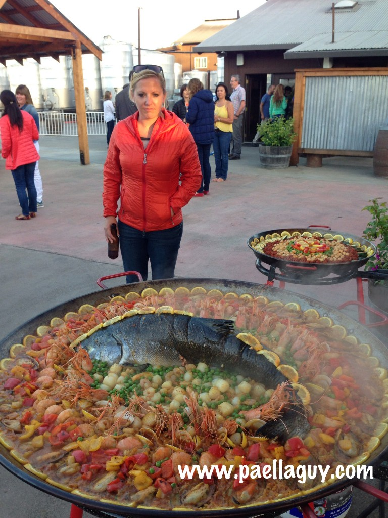 A guest with Camelbak admires Salmon Paella created by Paella Guy.