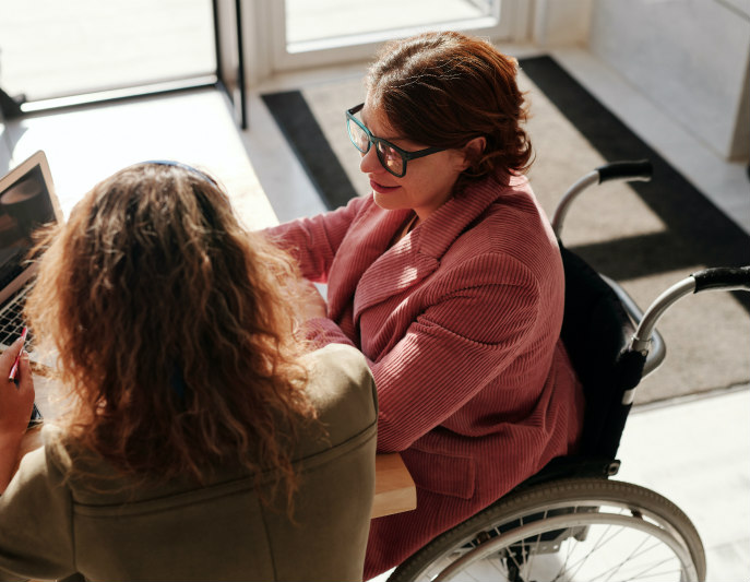 Woman in wheelchair working at desk with colleague