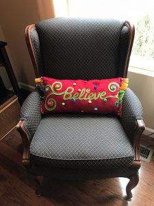 believe holiday pillow on chair