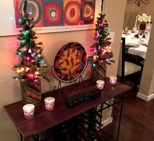 narrow table with bright lit Christmas trees