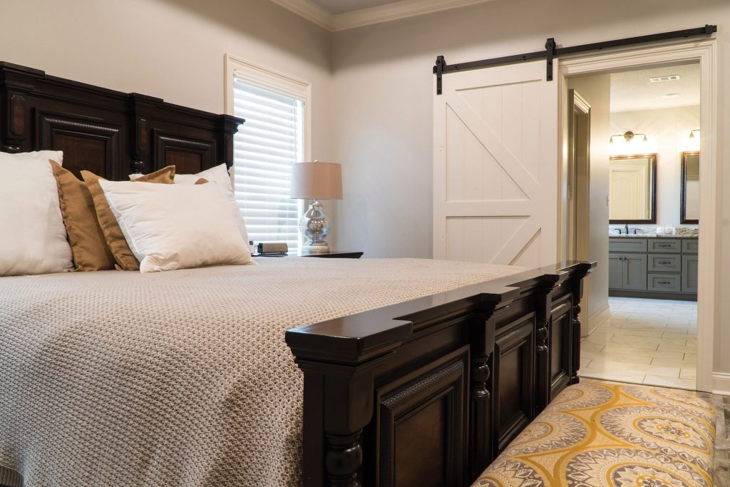 bedroom with barn door into bathroom