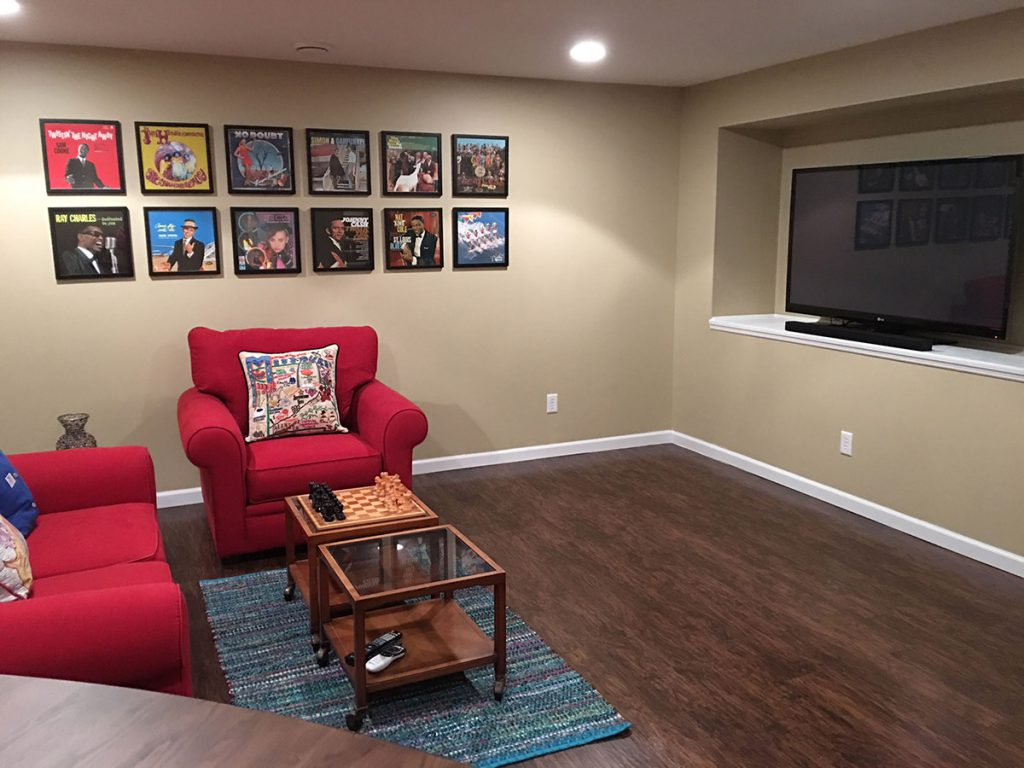 A fully furnished basement den with album art on the wall.