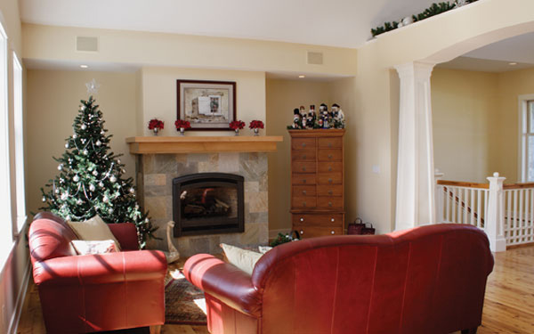 A living room with red furniture and a Christmas Tree.